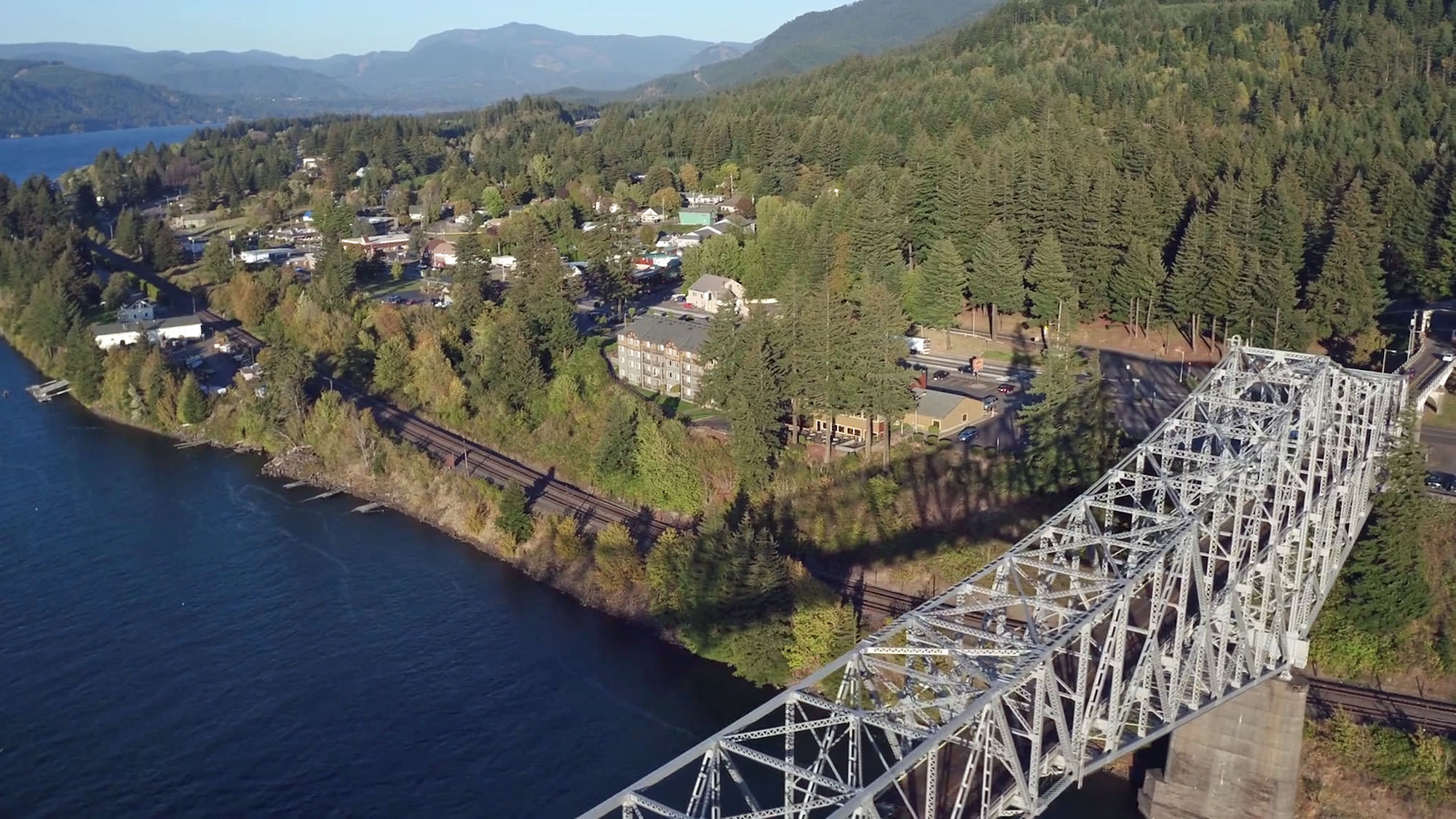 A bird's-eye view of Cascade Locks showcases the blue Columbia River, green trees and the impressive steel Bridge of the Gods.