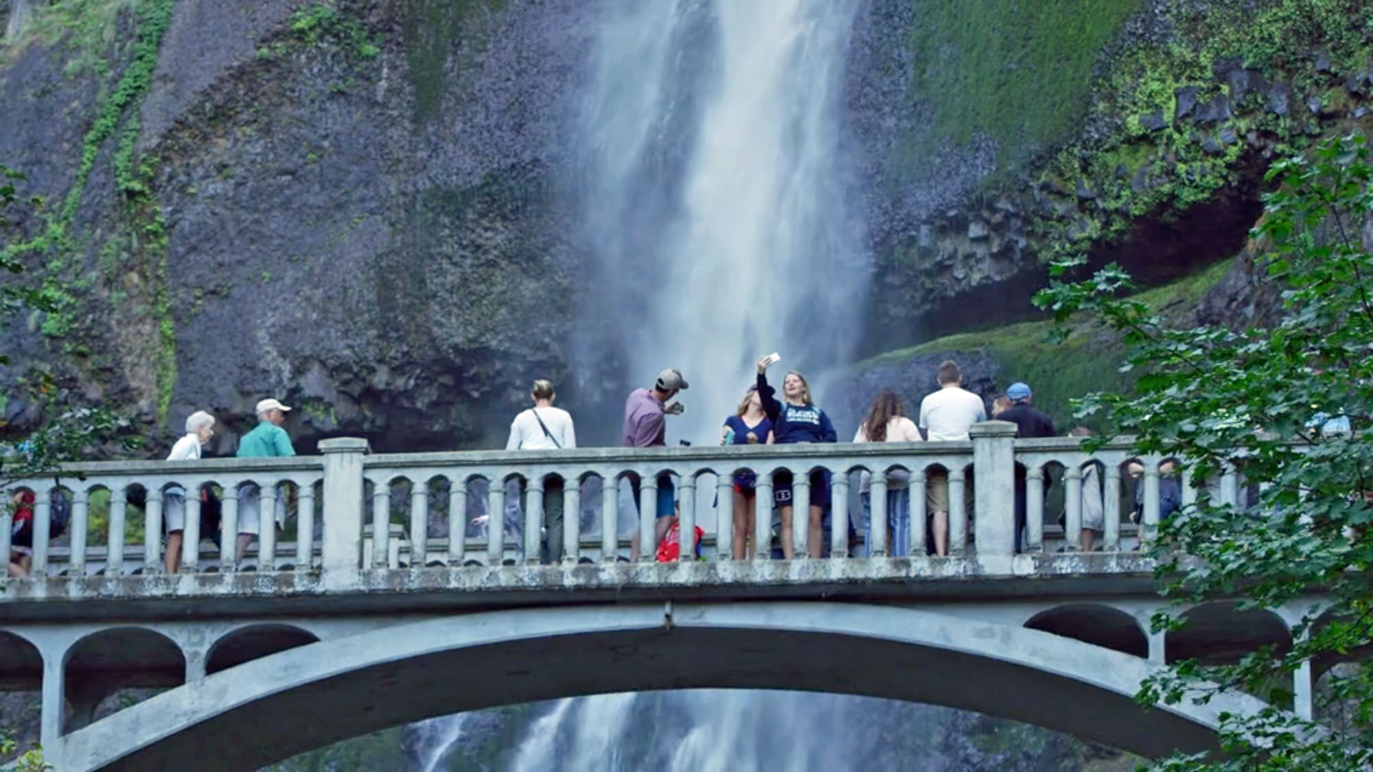 Visitors poses for selfies on Benson Bridge, with the Multnomah Falls cascade behind them.