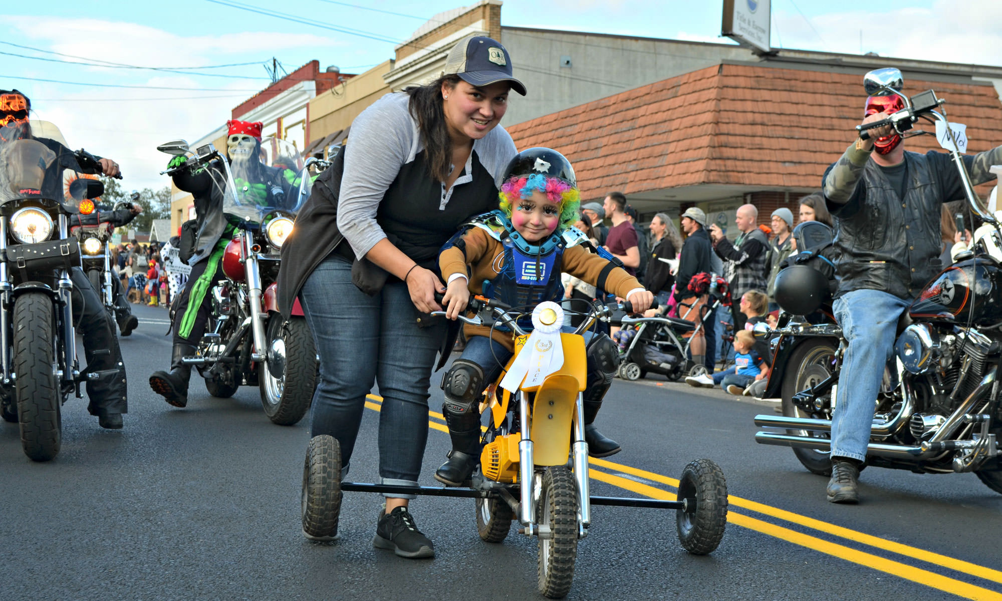 A child wearing a wig with face paint leads a motorcycle parade on her tricycle.