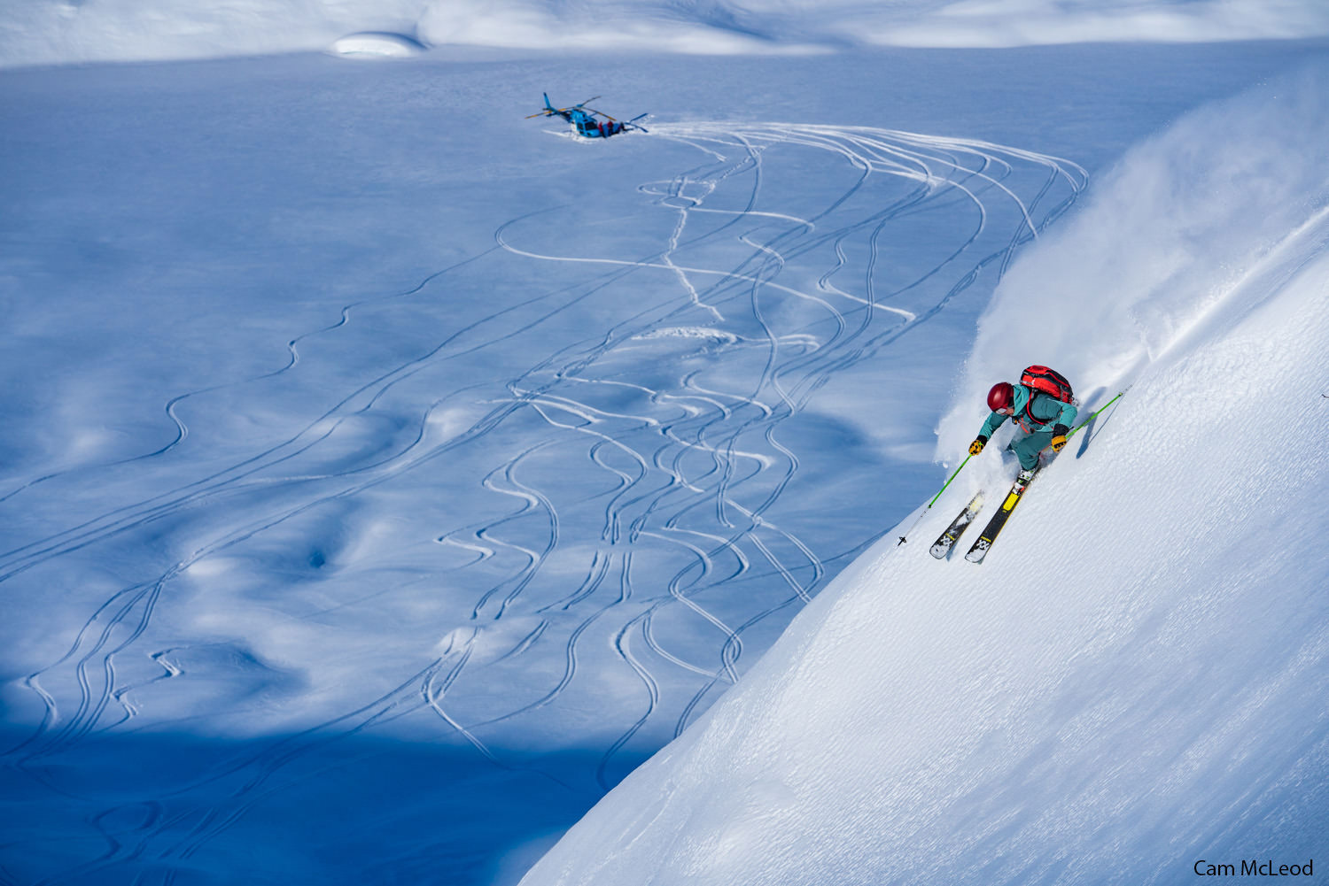 A skier descends a steep slope with a helicopter in the background.