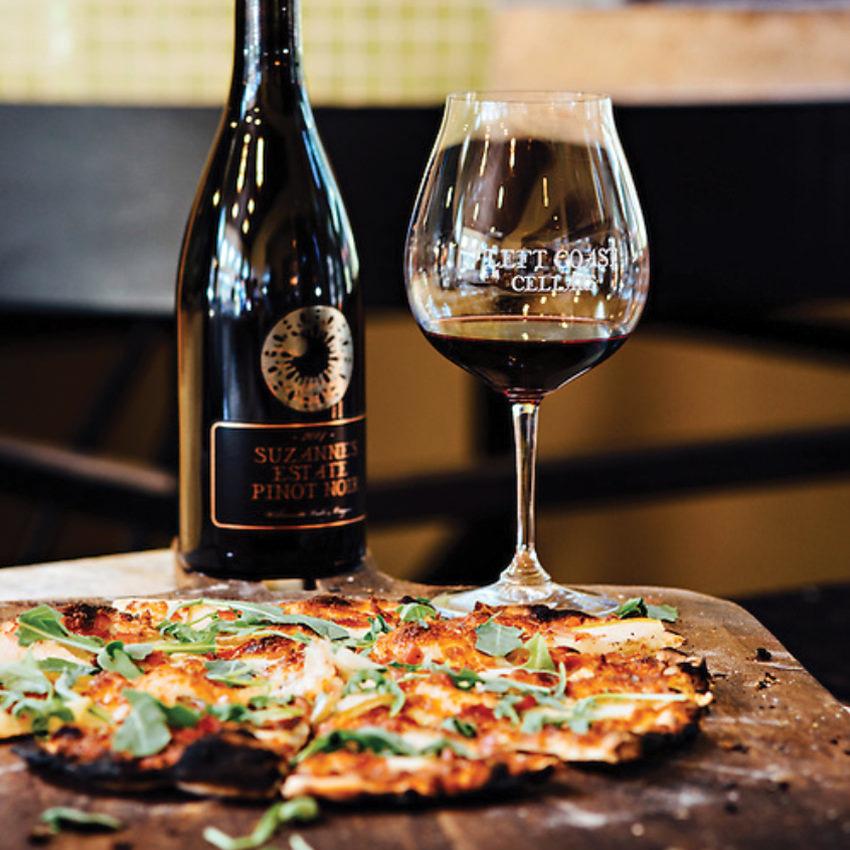 Flatcrust pizza with a glass of Left Coast wine