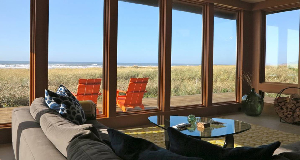 The interior of a beach side rental with chairs on the back porch overlooking the ocean
