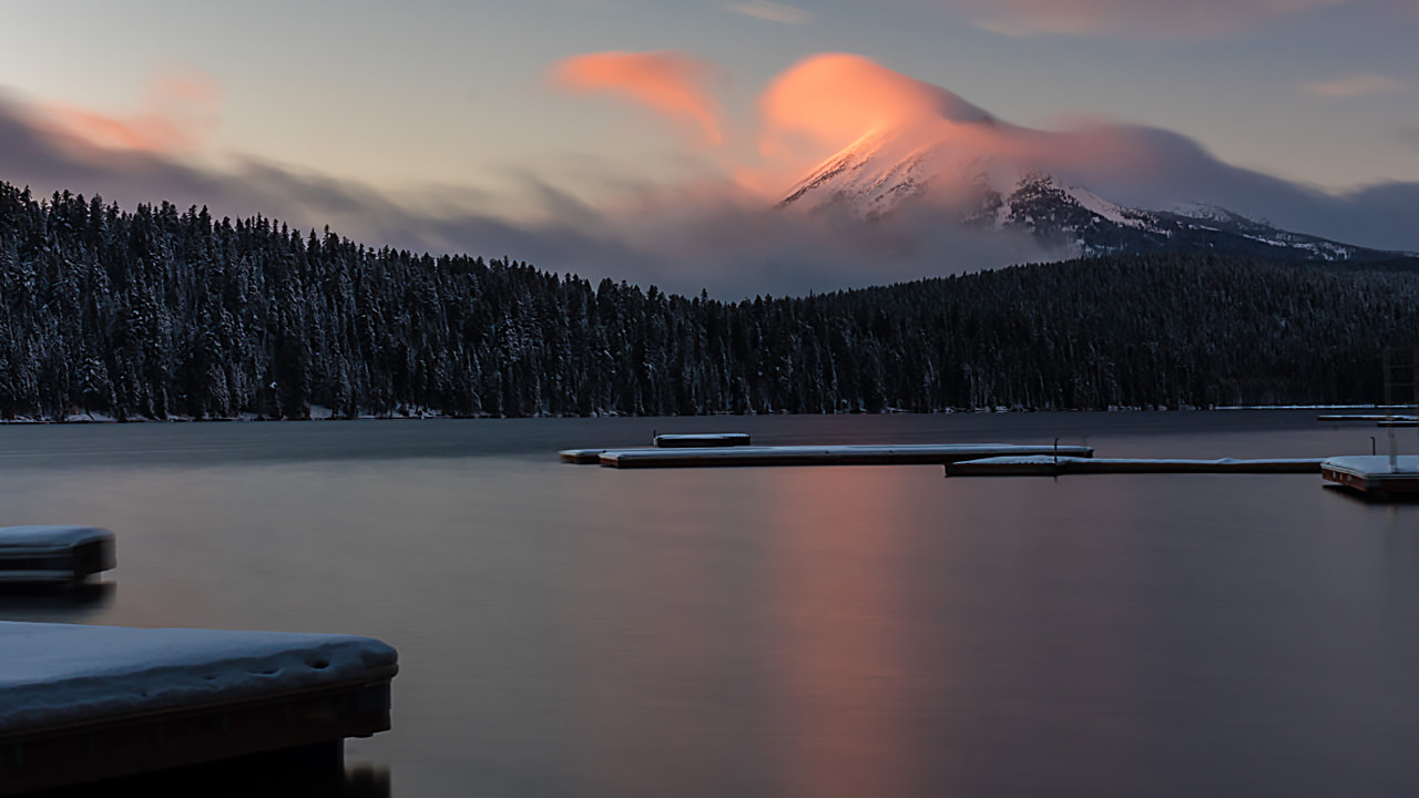 Sunrise at snowy lake with a mountain in the distance