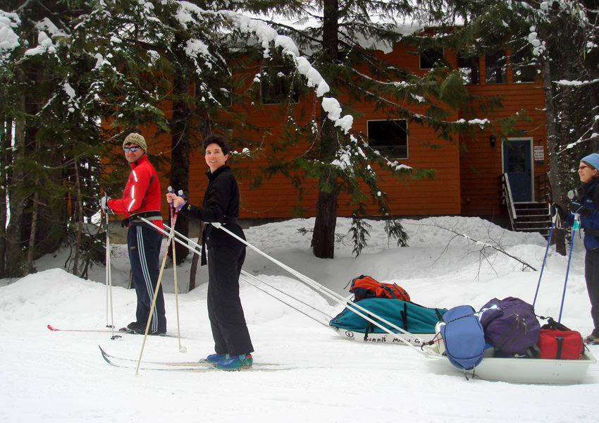 Two cross-country skiers pull sleds full of gear