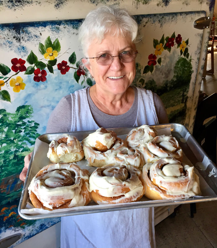 A woman holds a tray of large iced cinnamon rolls in front of a wall mural.