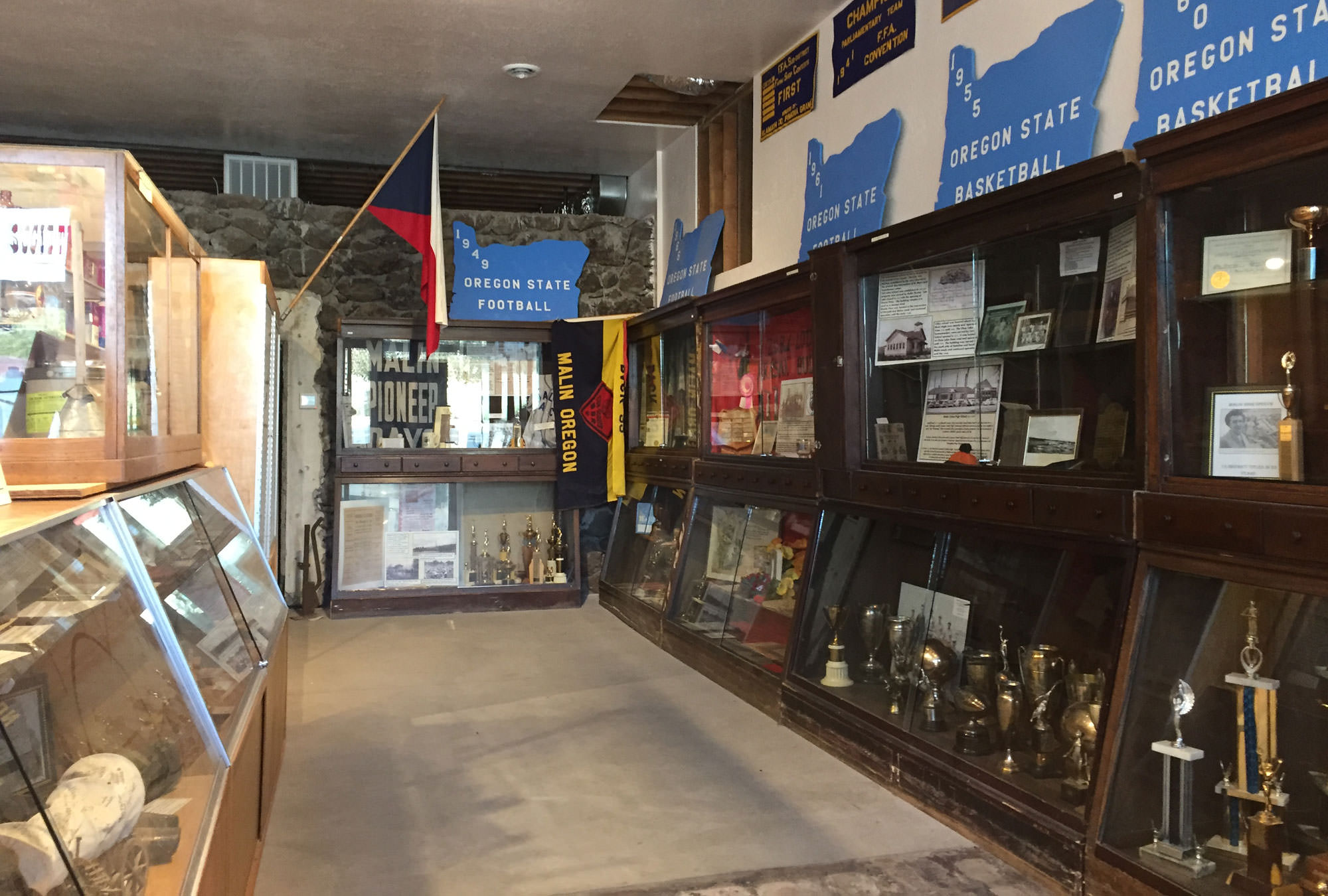 Basalt rock walls surround cases of local memorabilia, including basketball championship trophies.