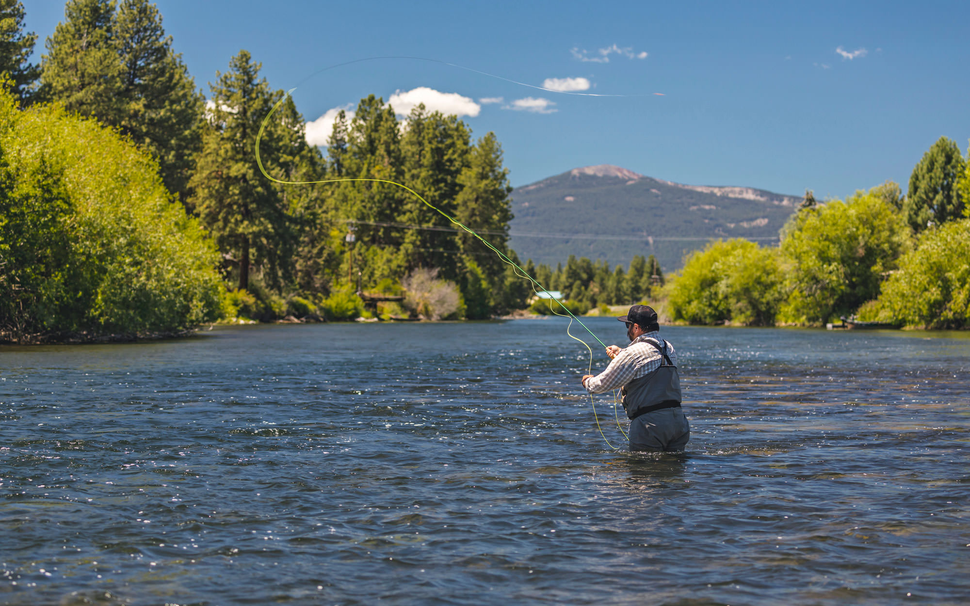 A fly fisher casts a line into the blue waters of the Lower Williamson River.