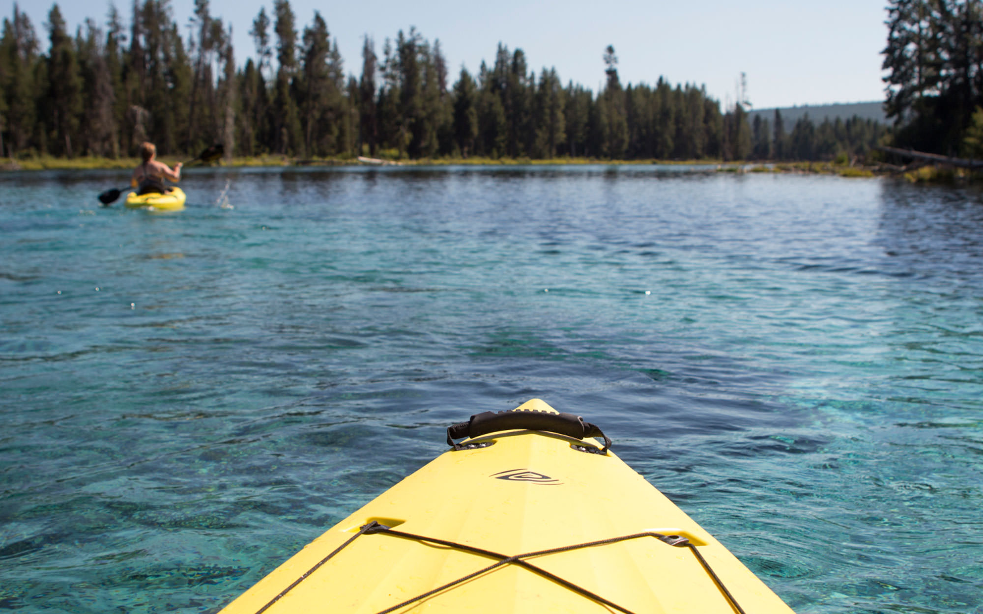 A kayker's perspective of Spring Creek shows clear blue waters and the yellow front of a kayak.
