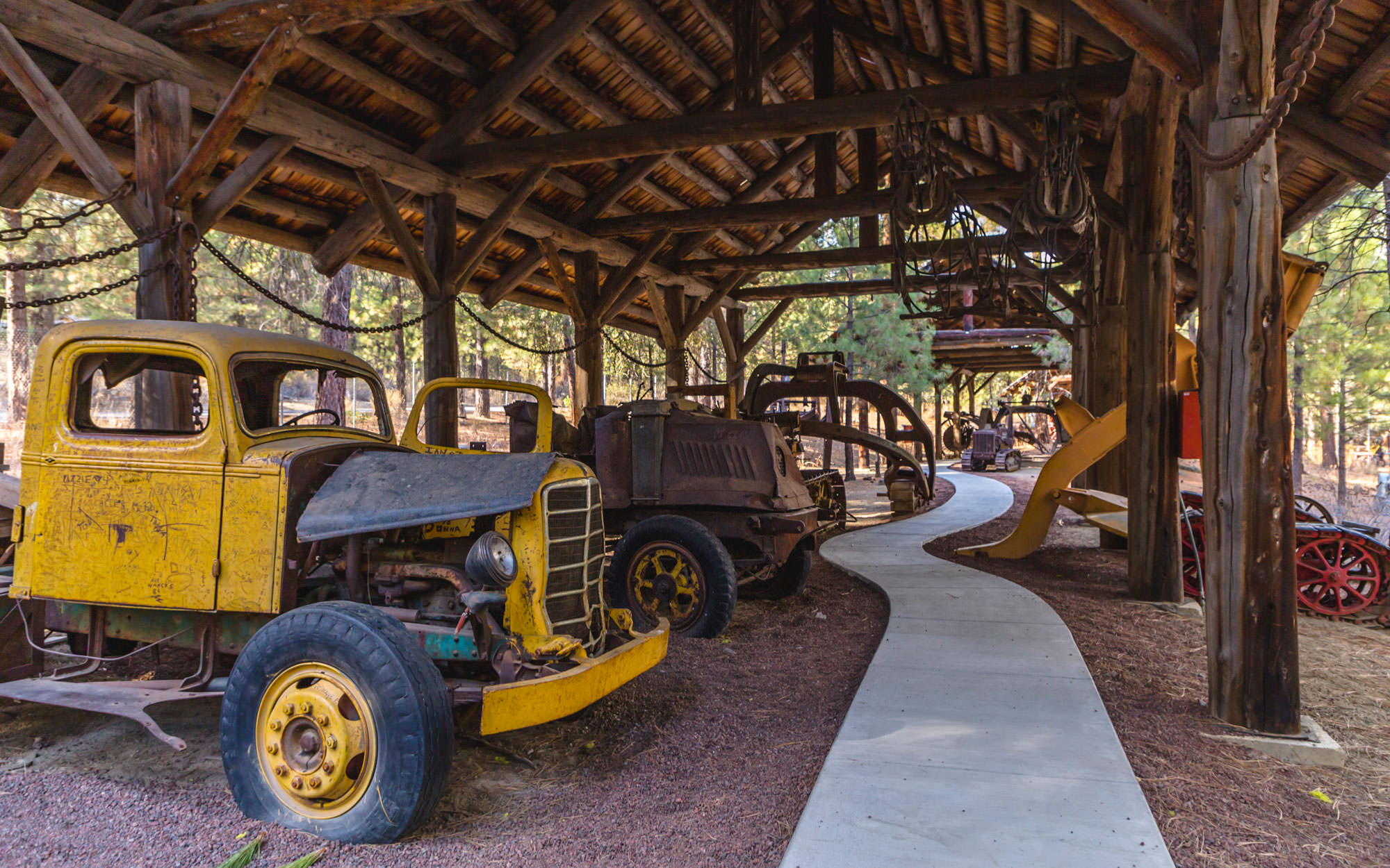 A paved path winds around antique logging machines.