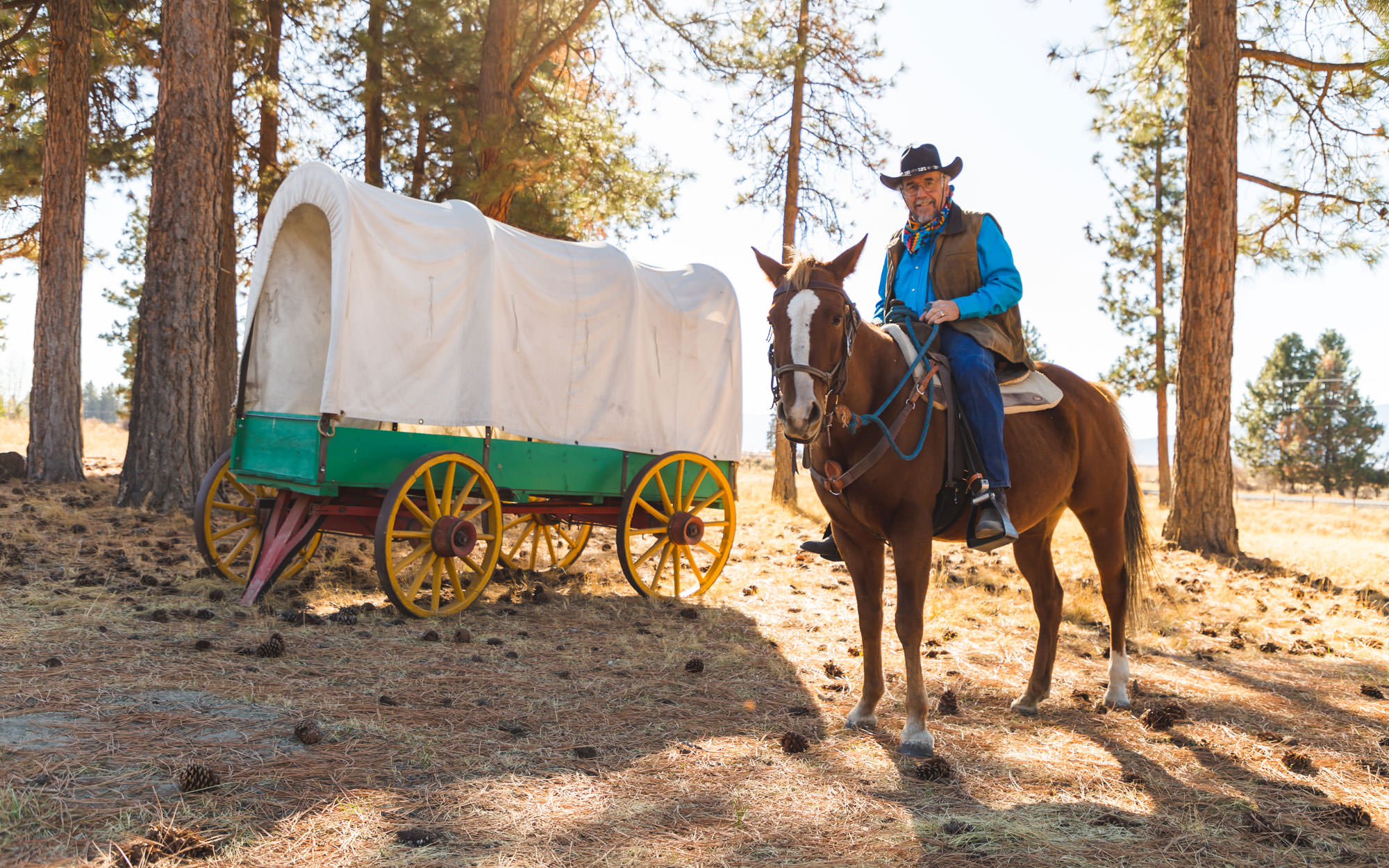 A man wearing a cowboy hat sits and smiles while riding a horse in front of a replica of an Oregon Trail wagon.