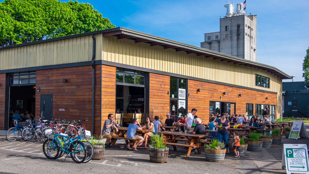 The exterior of Oakshire Public House shows a wooden brewpub with outdoor seating and bicyclists -- however the photo can't show the DJ spinning music or the fresh taps being poured.