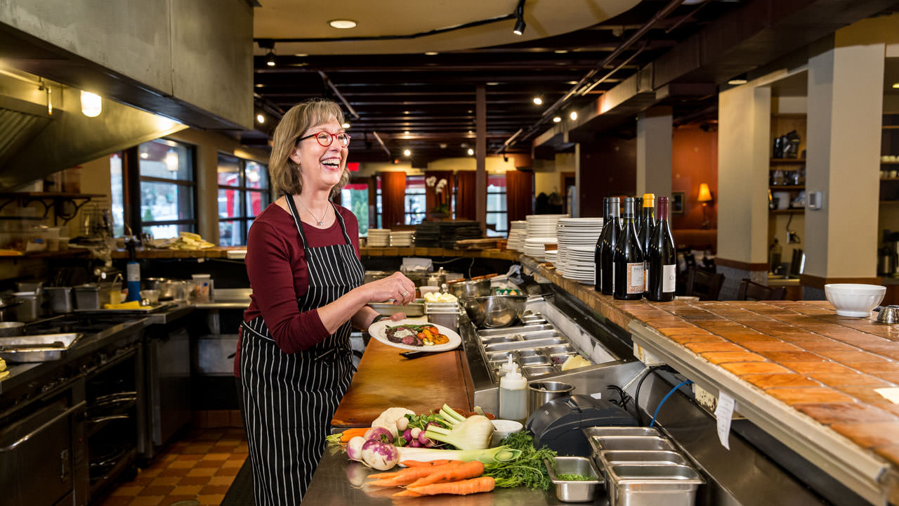 Chef Stephanie Pearl Kimmel laughs as she prepares a dish at Marché.