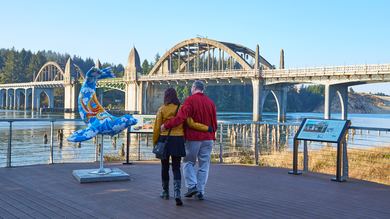 A couple walks with arms embraced as they approach a colorful sea lion sculpture in front of a bridge.