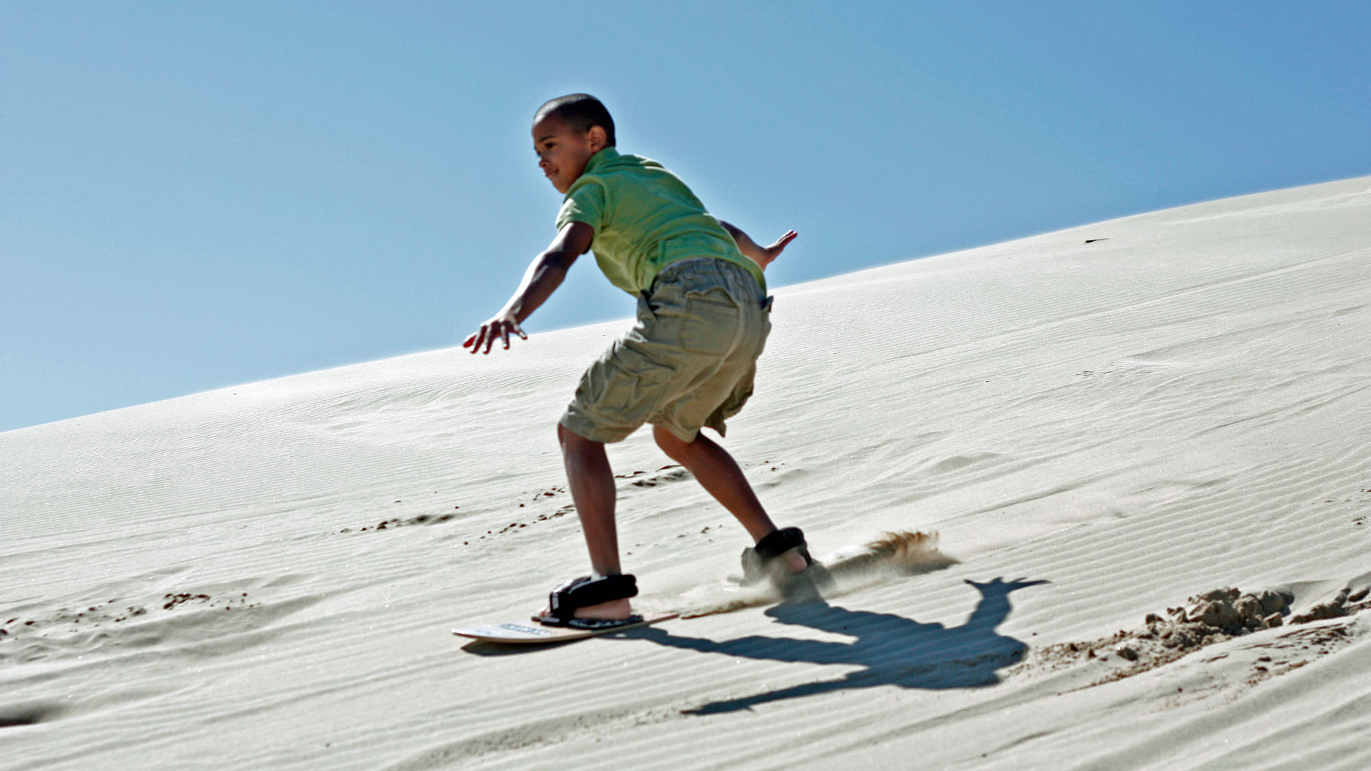 A kid slides down the Oregon Dunes on a sandboard.