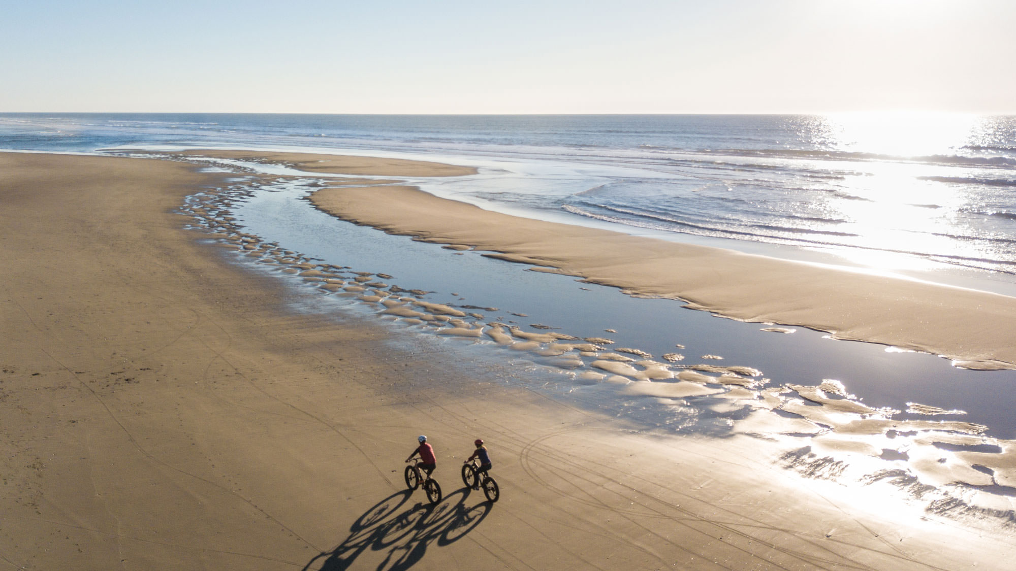 A bird's-eye view above beach fat bikers reveals a wide-open coastline with just cyclists in sight.