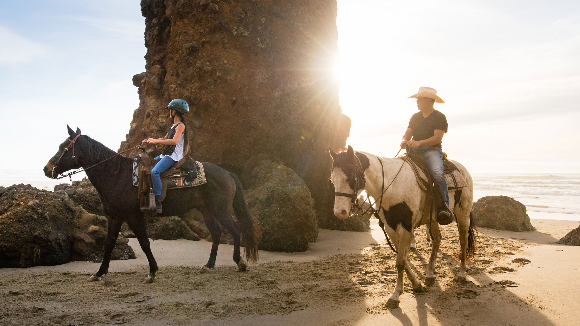A child and parent ride horses on the beach, with a large sea stack behind them.