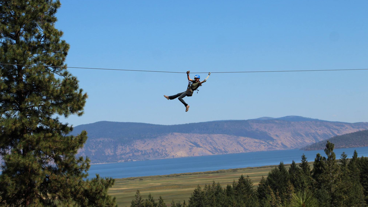 A person whizzes by on a zipline overlooking the blue waters of Klamath Falls.