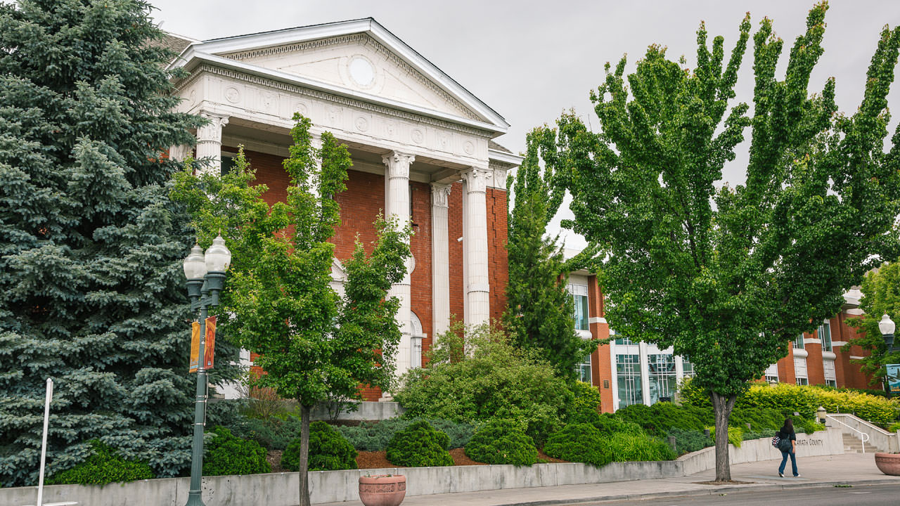 The Klamath Falls City Hall has tall white pillars and bright red brick exterior.