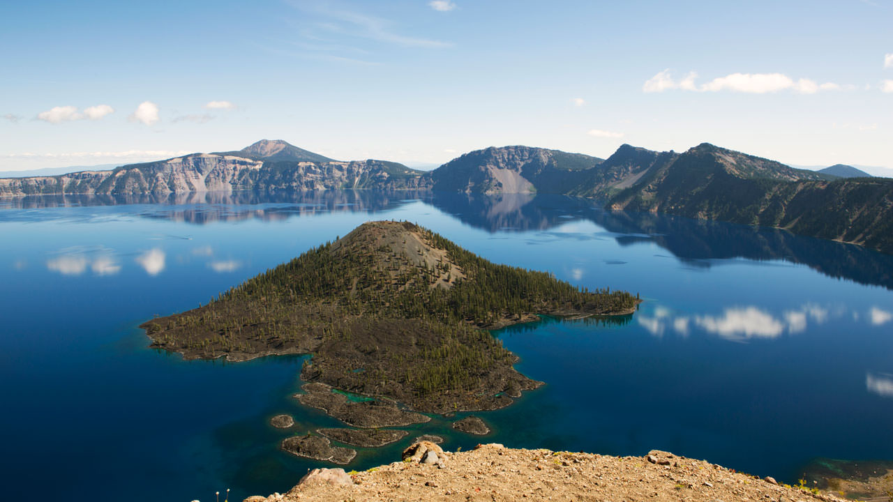 The brilliant blue waters of Crater Lake reflect images of clouds.