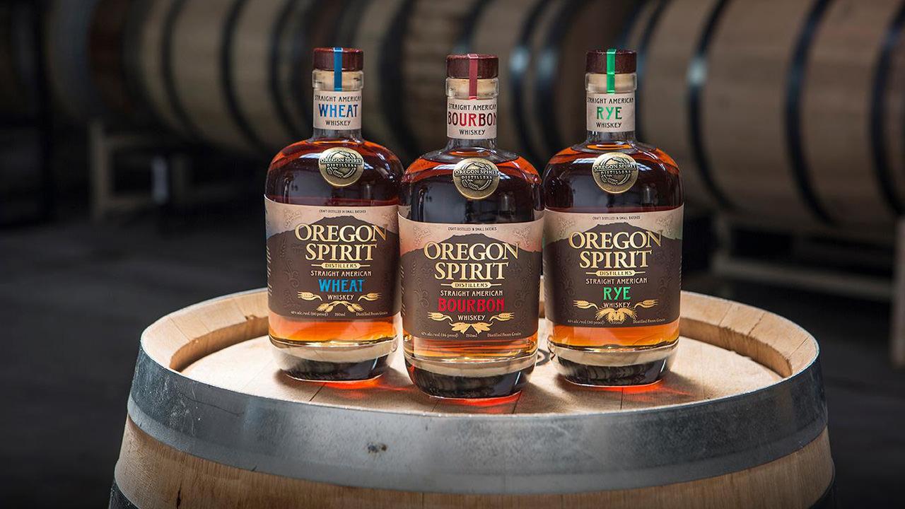 Three whiskey varieties of Oregon Spirit Distillers shine in cellar lighting.