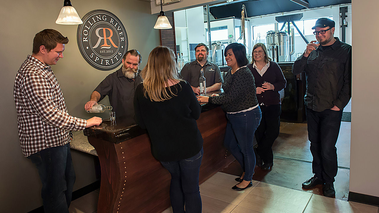 A group of guests smile around a bartender pouring spirits.