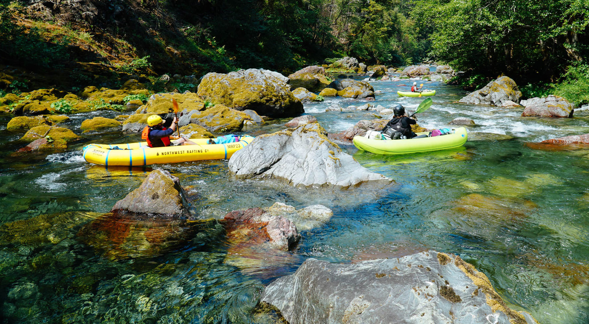Single rafters look down at the completely clear waters of the Chetco River.