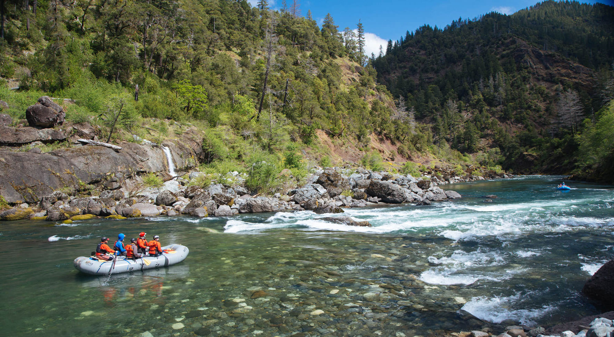 A rafting group cruises down the crystal-clear waters of the Illinois River.
