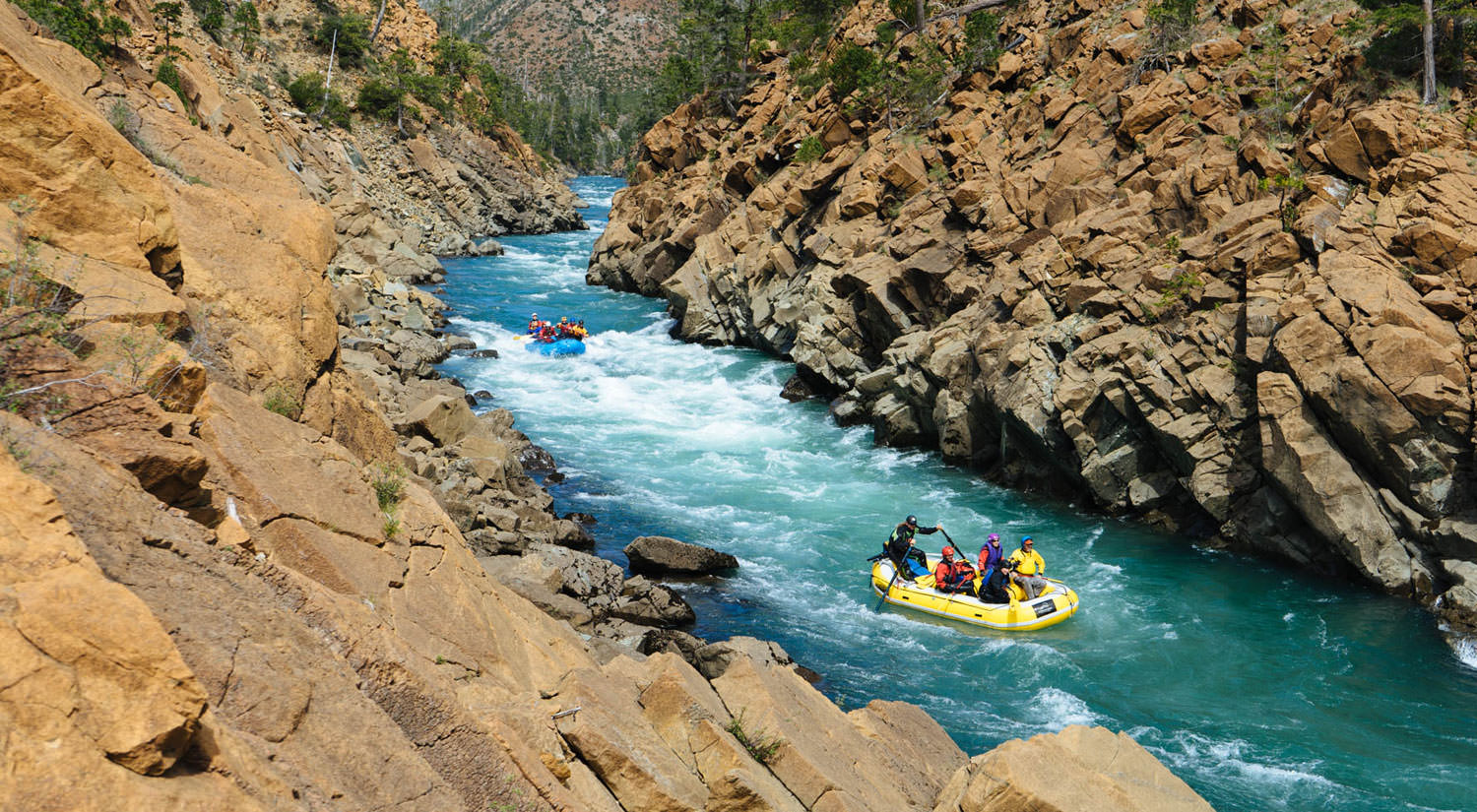Rafters on a bright-blue river stand out in a dry river canyon.