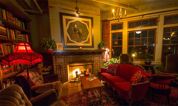 The interior of McMenamins Grand Lodge's Billy Scott Bar features vintage furniture, colorfully painted walls and a cozy fireplace.