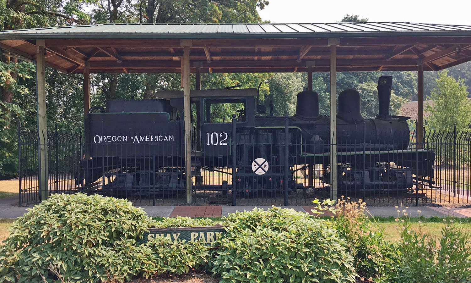 A retired black locomotive sits under a shelter in a green park.