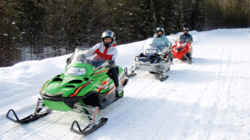 Three snowmobiles (and their riders) line up a groomed trail in the Mt. Hood National Forest.