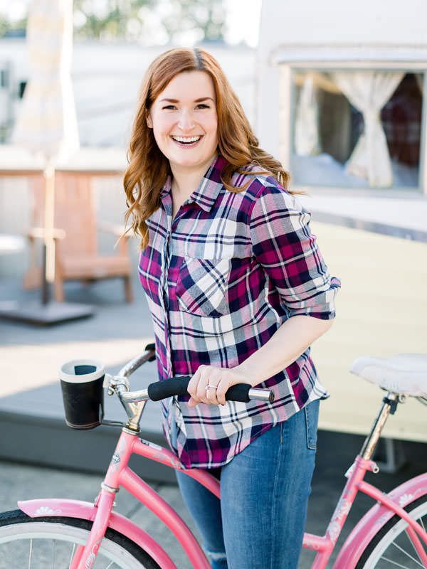 A redhead girl laughs while ready to ride her pink bike in front of a trailer.