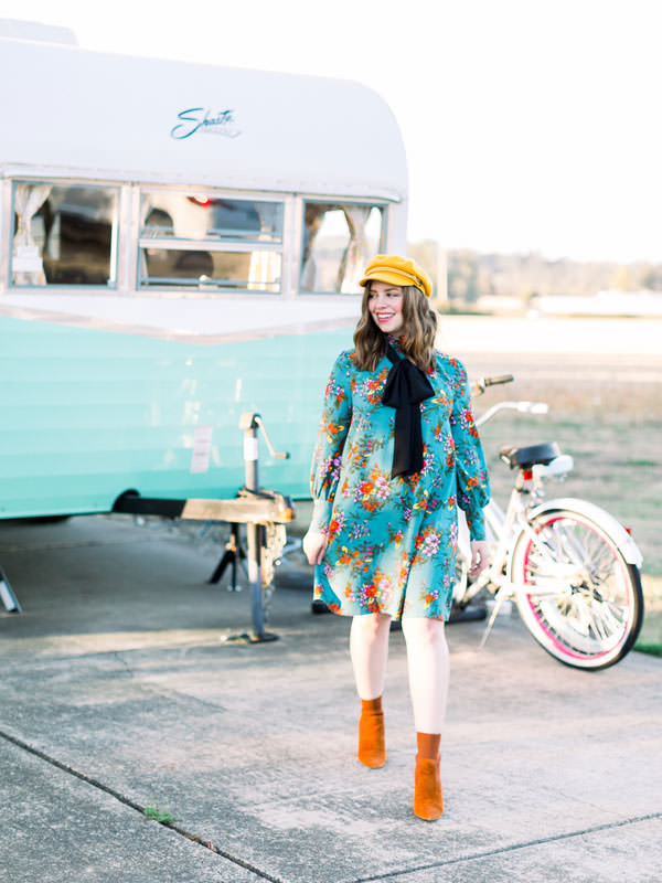 A stylish girl walks in front of a teal trailer.