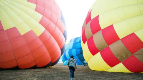 A girl walks between two deflated hot air balloons.