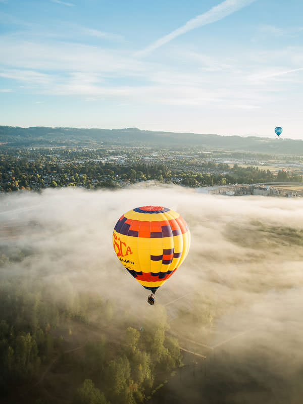 Hot air balloons float over the clouds.