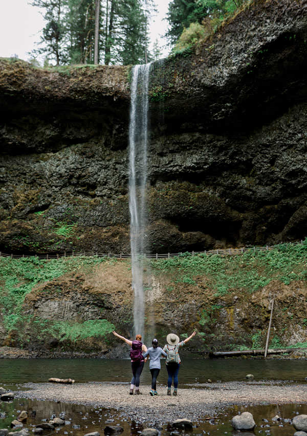 Three girls stand at the base of a waterfall, posing.