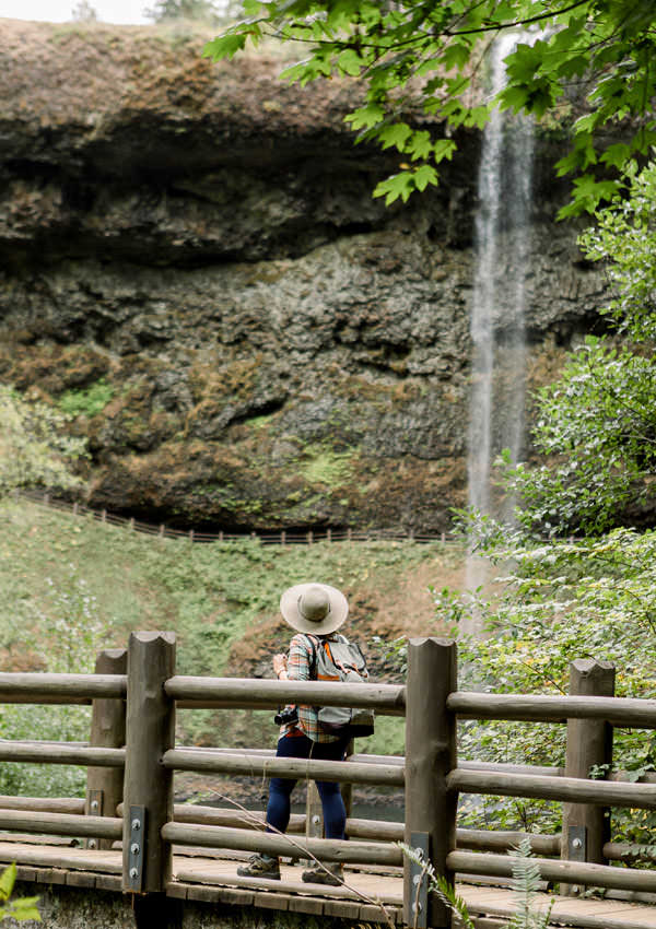 A girl looks up at a waterfall from a footbridge.