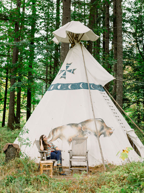 A girl lounges in a chair outside a teepee depicting buffalo.