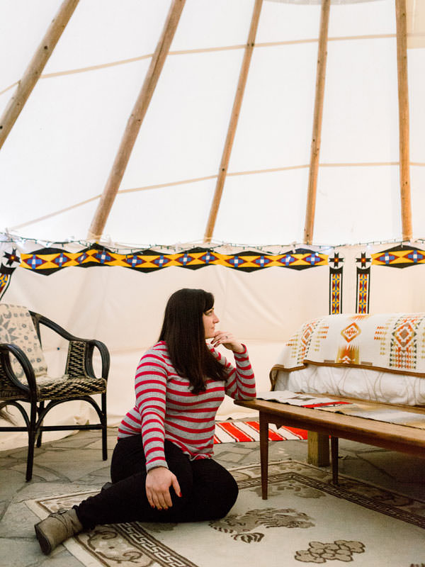 A girl rests on a carpet inside a stylishly decorated teepee.