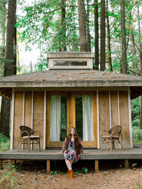 A girl sits in front of a cozy cottage in the forest.