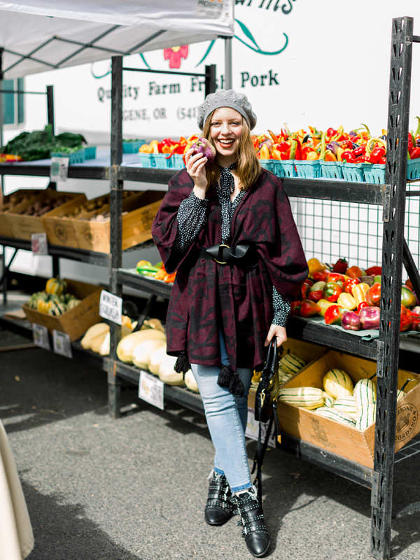 A girl smiles holding produce at a farmers market.
