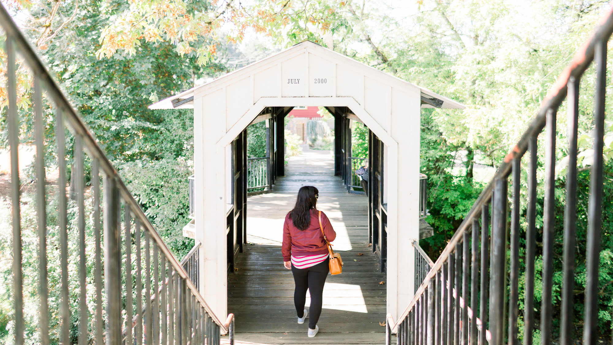 A girl walks down stairs into a covered bridge.