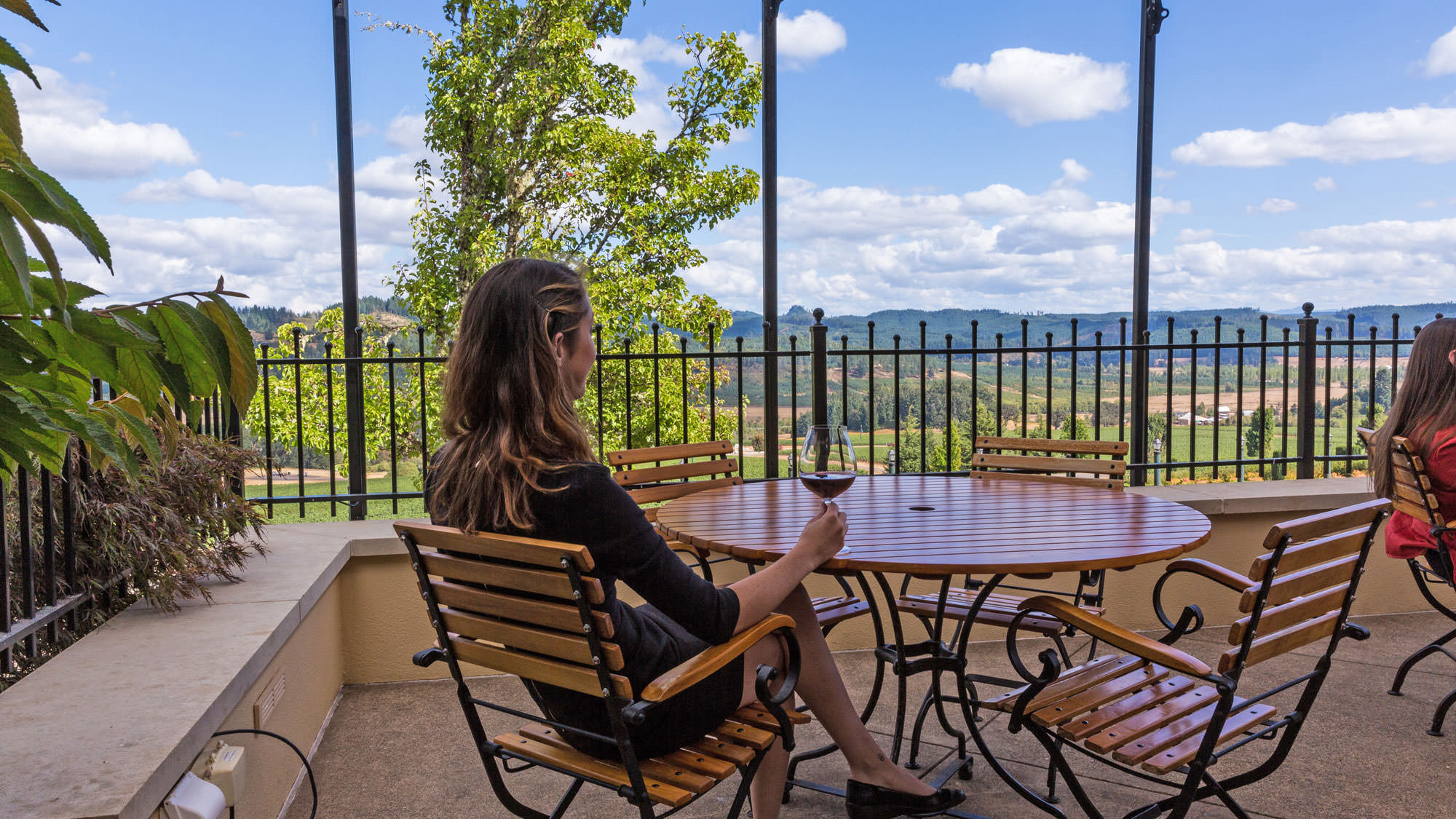 A girl holds a glass on pinot noir from the covered patio of King Estate.