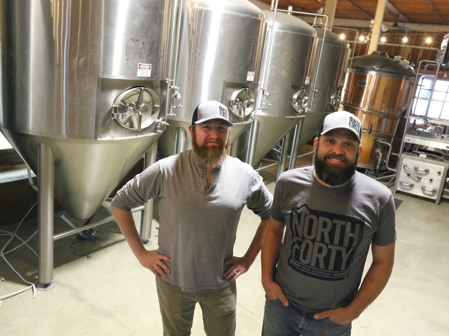 North Forty owners R.J. Mills and Arin Forrest smile for the camera in front of large brewing containers.