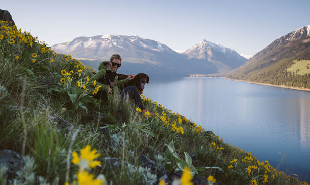 A girl sits amid yellow wildflowers and two dogs overlooking the blue waters of Wallowa Lake.