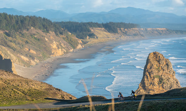 Two bicyclists pedal down a hill overlooking the dramatic coastline.