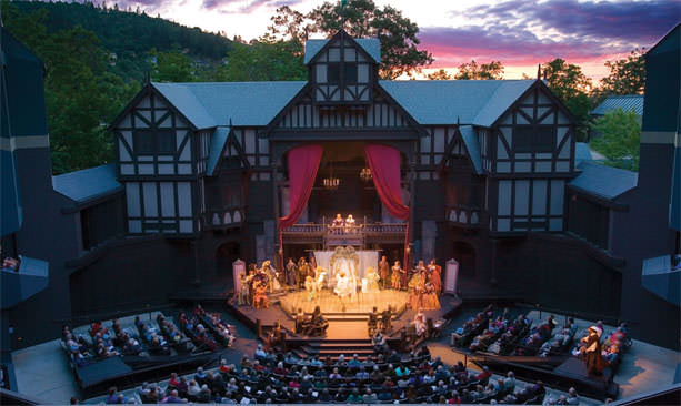 A stage is illuminated with a Victorian-style backdrop under open skies at sunset.