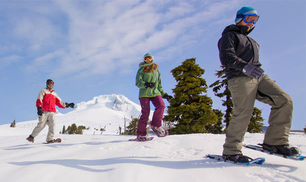 Three brightly covered snowshoers smile with Mt. Hood's snowy peak in the background.