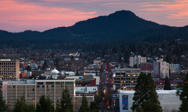 Sunset paints a pink sky over the woodsy city of Eugene.