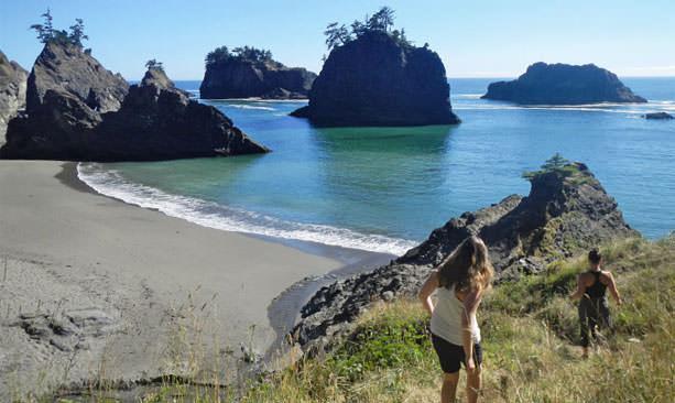 Two girls walk down a grassy path to a hidden beach where sea stacks loom tall.